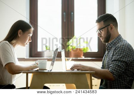 Work Rivals Feeling Jealousy, Envy, Looking At Each Other Behind Laptops, Competing In Developing Bu