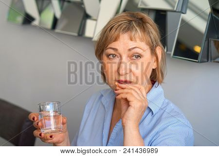 Sick Elderly Woman Holding Pill Glass Of Water At Home On The Sofa. Depressed Unhealthy Woman, About
