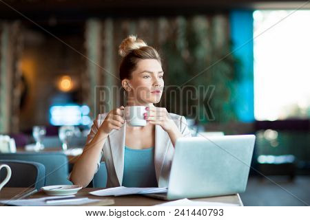 Young pensive businesswoman with cup of tea or coffee thinking of working ideas in front of laptop in cafe
