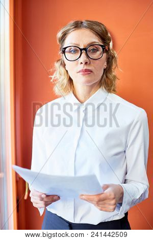 Mature serious business lady in formalwear and eyeglasses looking at you while working with financial papers