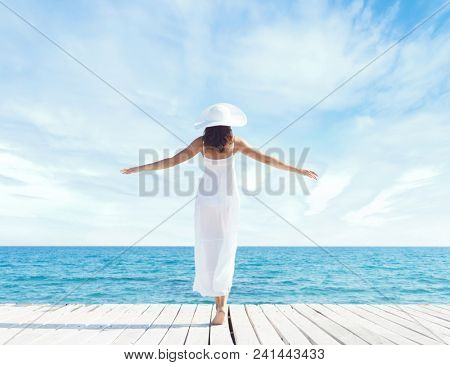 Young, beautiful and healthy girl on wooden pier at summer.