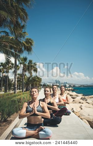 Full Length Portrait Of Orderly Girls Doing Meditation Near Ocean. They Keeping Arms Together