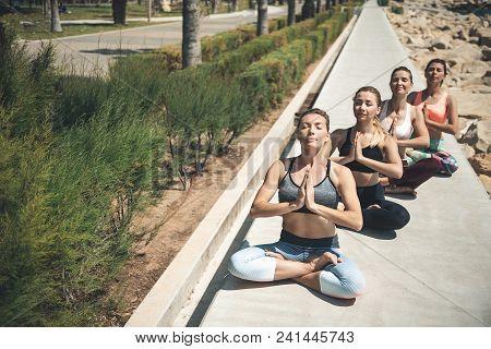 Full Length Portrait Of Orderly Girls Doing Meditation While Locating In Park. Calm Females Demonstr