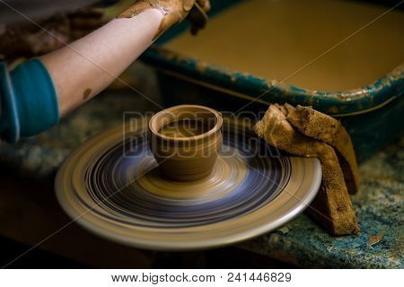 clay pot closeup. Modeling clay close-up. Caucasian man making vessel daytime of white clay in fast moving circle. Art, creativity. Ukraine, cultural traditions poster