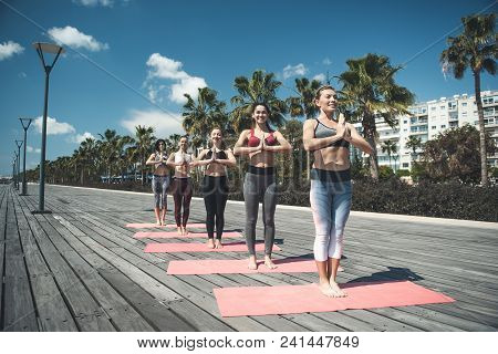 Full Length Portrait Of Cheerful Women Practicing Yoga In Nature. Happy Comrades During Training Con