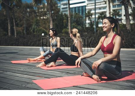 Full Length Outgoing Girls Meditating During Gymnastic Exercise. They Sitting On Mats On Seafront. C