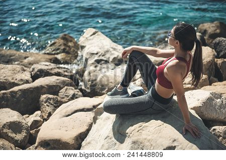 Full Length Side View Pleased Lady Resting After Long Jogging. She Sitting On Sea Shore. Glad Girl R