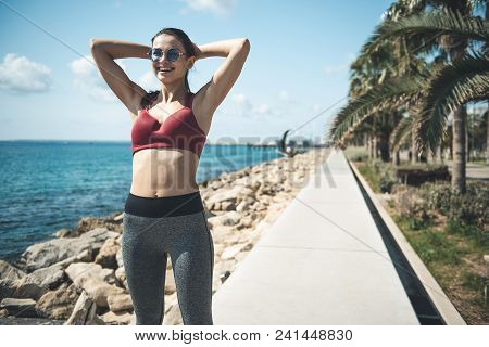 Portrait Of Outgoing Woman Relaxing After Physical Exercise On Open Air In Park With Palm Trees And