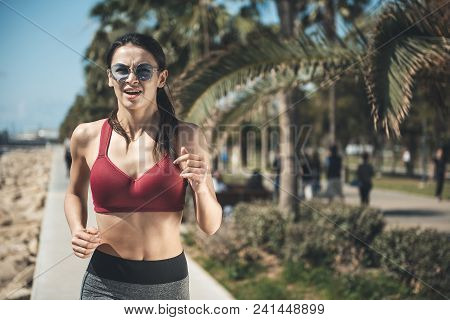Portrait Of Happy Girl Running Under Hot Sun In Park With Palm Trees. Happy Lady Making Exercise Con