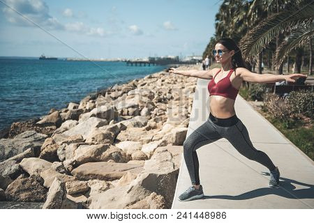 Full Length Portrait Of Cheerful Woman Gesticulating Hands While Stretching Body Near Water. Pleased