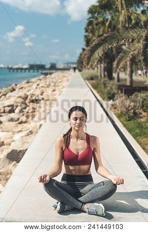Full Length Portrait Of Smiling Woman Making Yoga Exercise While Situating On Sea Shore. Meditation