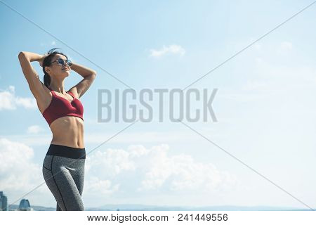 Portrait Of Smiling Lady Resting Against Blue Sky After Working Out. Happy Girl Practicing Gymnastic