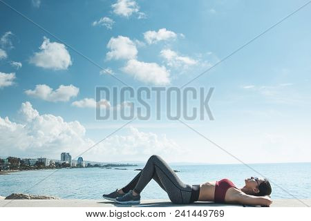 Full Length Side View Outgoing Woman Lying On Beach Near Blue Sea After Gymnastic Exercises. Rest In