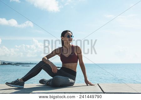 Full Length Portrait Of Cheerful Young Lady Relaxing After Doing Sport Outdoor. Leisure After Workou