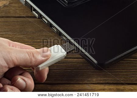 The Hand Inserts A White Usb Flash Drive Into The Input Of A Black Laptop, Close-up