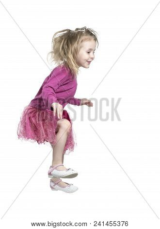 Little Beautiful Girl With Disheveled Hair Jumping, Sideways To The Camera, Isolated On White Backgr