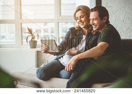 Portrait Of Happy Family Is Making Selfie On Tablet. Man Is Embracing Pregnant Woman And Smiling. Th