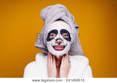 A Funny Young Girl With A Towel On Her Head And In A Dressing Gown Looks After The Skin Of The Face,
