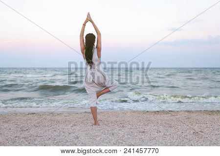 Yoga Meditation Woman With Dreadlock Meditating At Beach Sunset Relaxing In Yoga Posture, Tree Pose,