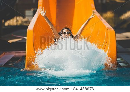 Joyful Woman Going Down On The Rubber Ring By The Orange Slide Make The Water Splashing In The Aqua