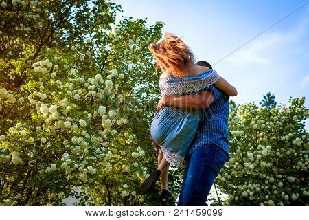 Happy Couple In Love Having Fun In Blooming Garden. Man Holds His Girlfriend In Hands And Spins At S
