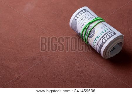 100 Dollar Bills Twisted Into Tube And Tied With An Elastic Band. Copy Space For Text