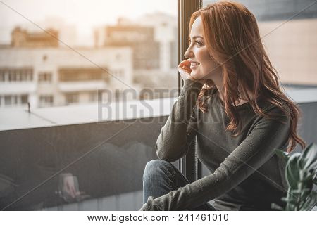 What Comes Next. Side View Of Happy Girl Sitting On Windowsill. She Is Admiring Picturesque Panorama