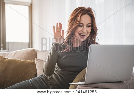 Hello. Waist Up Portrait Of Cheerful Girl Sitting On Her Couch At Home. She Is Waving Hand With Smil
