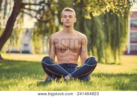 Healthy Lifestyle Concept. Shirtless Young Man In Meditating In Lotus Pose Sitting On Green Grass.