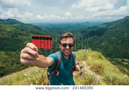 Young Smiling Male Showing Empty Credit Card. He Is Standing On Top Of Mountain And Showing The Outd
