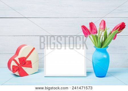 Colorful Red Spring Tulip Flowers In Nice Blue Vase And Blank Photo Frame With Decorative Heart Gift