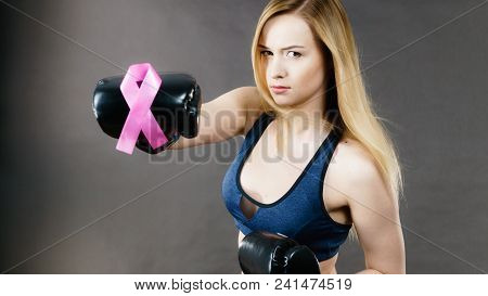 Young Sporty Woman Wearing Boxing Gloves Having Pink Ribbon Tape, Breast Cancer Symbol. Fighting Wit