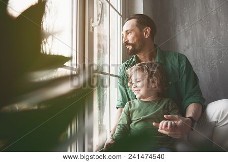 Portrait Of Smiling Dad And Outgoing Kid Looking At Window While Locating In Apartment