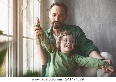 Portrait Of Happy Father Gesticulating Hands Of Beaming Child In Room