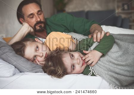 Portrait Of Tired Man Hugging Smiling Sons. They Relaxing On Cozy Bed In Room