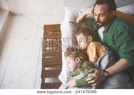 Top View Happy Father Embracing Serene Tired Kids While Resting In Room