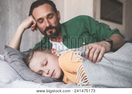 Portrait Of Smiling Dad Hugging Sleeping Son While Lying In Bed