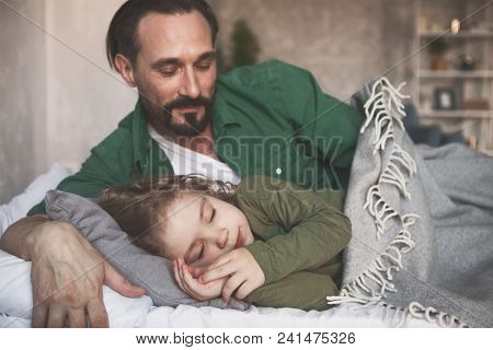 Portrait Of Smiling Dad Looking At Calm Sleeping Son In Apartment