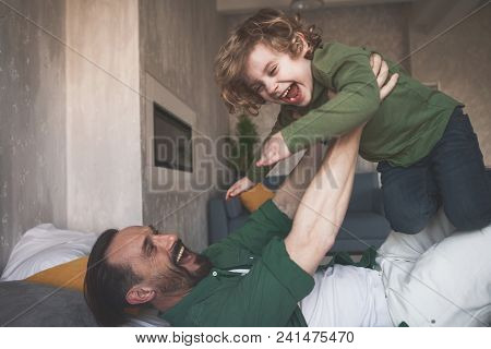 Portrait Of Happy Father Fooling Around With Glad Child On Cozy Bed In Room
