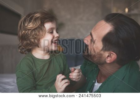 Side View Laughing Son Talking With Outgoing Father While Looking At Him In Apartment