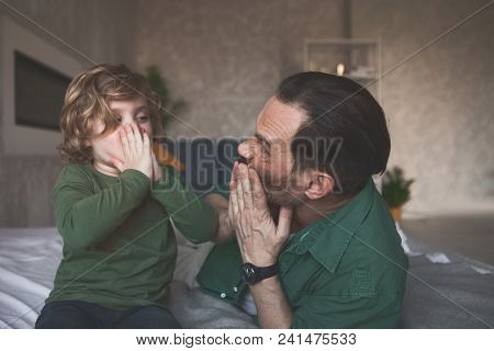 Happy Man And Cheerful Child Closing Faces By Hands While Relaxing In Room