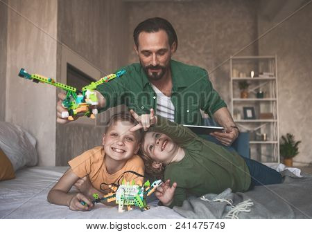 Portrait Of Satisfied Children Spending Funny Time With Cheerful Father While Relaxing On Bed. Paren