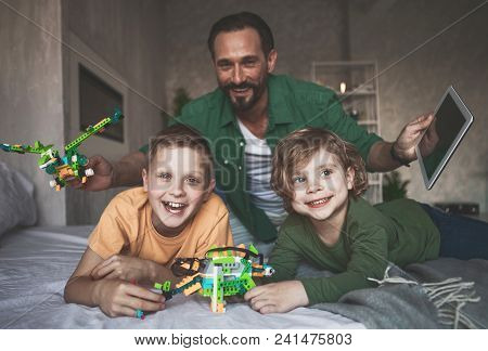 Portrait Of Smiling Children Having Fun With Laughing Dad In Apartment. He Holding Electronic Tablet