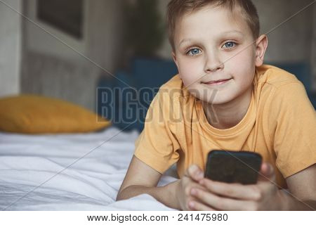 Portrait Of Smiling Small Child Using Digital Device While Relaxing On Cozy Bed In Room. Glad Boy Re