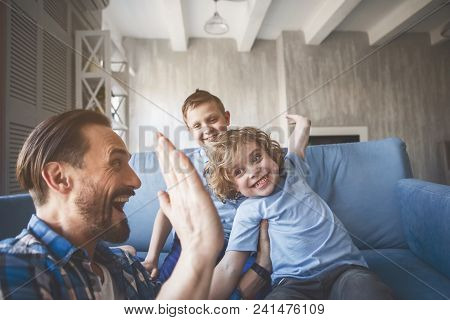 Outgoing Child Giving High Five For Laughing Dad. Cheerful Elder Brother Sitting Near Him. Satisfied