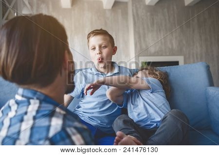 Outgoing Kid Demonstrating Tongue To Father While Having Fun With Little Laughing Brother. Cheerful
