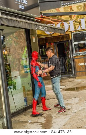 Seoul, South Korea; May 18, 2018: Unidentified Asian Man Setting Up Spiderman Figure In Front Of Sto