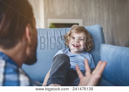 Portrait Of Laughing Child Looking At Dad While Sitting On Sofa In Room. He Gesticulating Hands