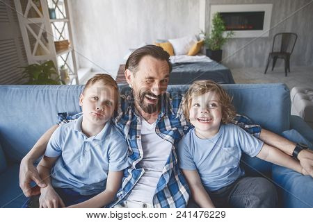 Top View Portrait Of Happy Dad Winking While Hugging Kids On Couch In Apartment