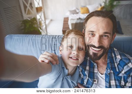 Portrait Of Cheerful Bearded Parent And Happy Child Making Photo By Camera